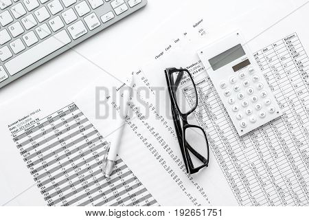 Business report preparing with calculator and glasses on white office desk background top view