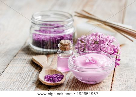 lilac cosmetics with flowers and homemade spa set on wooden table background