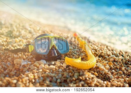 The snorkel mask on the sand with the beach background.