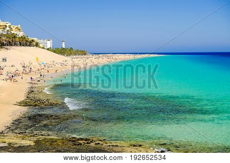 View on the beach Playa de Morro Jable in a sunny day with many people swimming in crystal water of the Atlantic ocean. Location Morro Jable on the Canary Island Fuerteventura Spain.