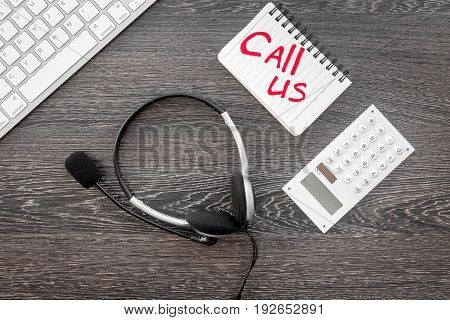 customer support service desktop with contact us copy on wooden background top view