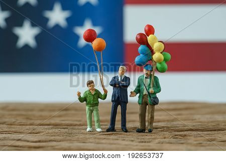 miniature people happy american family holding balloon standing with the president with United State national flag in the background as celebrating the Independence day.