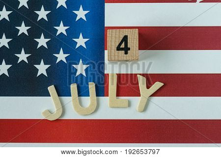 celebrating the Independence day with wooden block and alphabet as 4 July with United State national flag in the background.