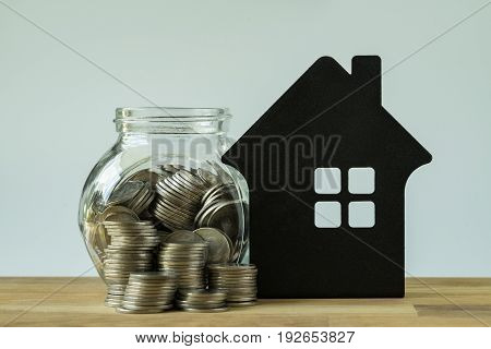 stack of coins and coins in glass pot with paper house on wooden table as financial saving target concept.