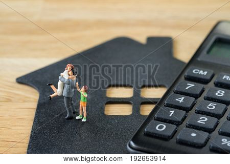 Miniature happy family figure standing on paper house with calculater as property or financial investment plan concept.
