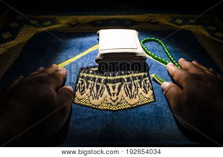 Holy Quran with beads on a prayer mat Muslim Tasbih is a string of prayer beads which is traditionally used by Muslims along with the Quran. Ramadan holidays concept. Selective focus