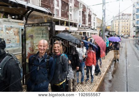 Lisbon Portugal - 5/10/2017: Tourists waiting in line for tram 28 under the rain.