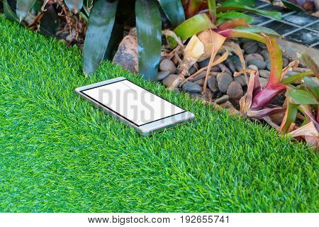 Mobile phone on artificial grass green background