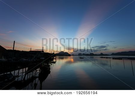 longtail boat with coastal fishing village Beautiful morning sunrise over sea and mountain in phang - nga thailand