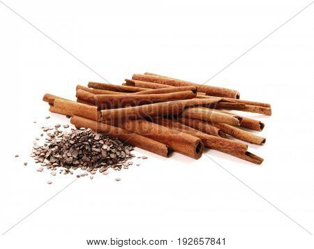 Cinnamon sticks and grated chocolate on white background.