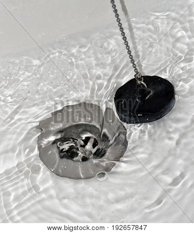 Draining water with the drain rubber plug on shower bath.