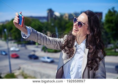 Mid shot of gorgeous madam taking selfie on top of building