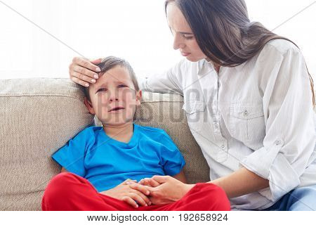 Close-up shot of young Caucasian mom soothing crying son. Carrying mother sitting with son