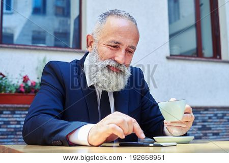 Mid shot of joyful sir surfing in phone over cup of coffee