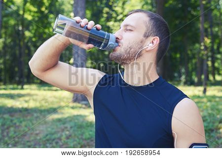 Close-up shot of a male drinking water; wearing sport cloth; closing eyes. Man having good posture and shape