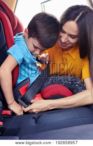 Vertical of caring mother helping son sitting in baby seat to fasten seat belt