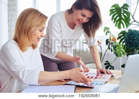 Close-up of smiling brunette and blonde working with catalog of color palette