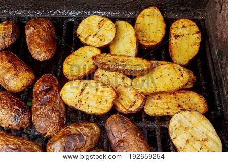 Big Slice Of Village-Style Potatoes On Hot BBQ Charcoal Grill. Flames of Fire In The Background. Tasty Snack For Outdoor Summer Barbecue Party Or Picnic.
