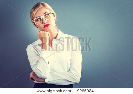 Unhappy young woman on a gray background