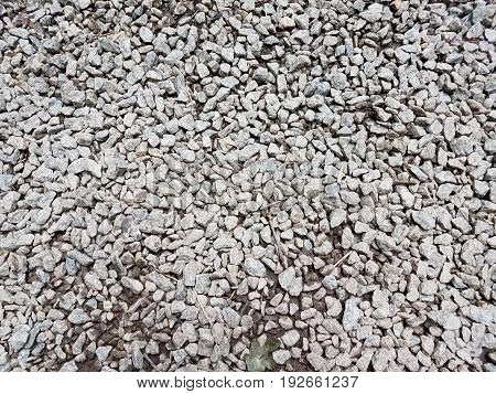 many small grey pebbles or stones on the ground