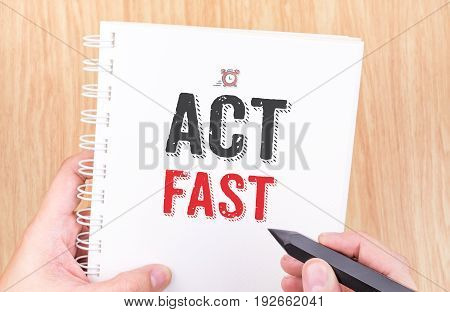 Act Fast Word On White Ring Binder Notebook With Hand Holding Pencil On Wood Table,business Concept