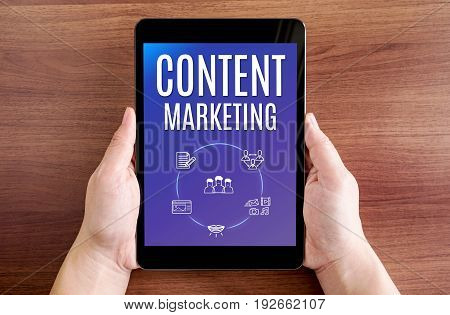 Two Hand Holding Tablet With Content Marketing And Icon On Screen At Dark Brown Table Top,digital Bu
