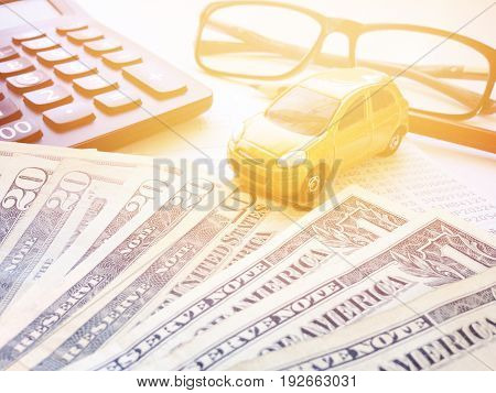 Business, finance, savings, banking or car loan concept : Miniature car model, pencil, calculator, eyeglasses, money and savings account passbook or financial statement on white background