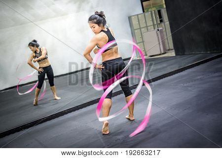 beautiful young asian female gymnast with pink ribbon in fitness gym gymnastics exercise concepts