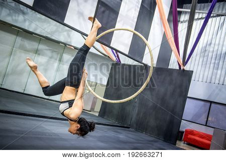 young asian acrobatic woman doing her gymnastics performance on aerial hoop or aerial ring