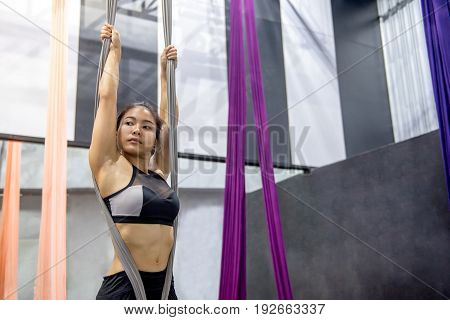 Young Asian woman doing anti-gravity yoga or fly yoga in aerial gym