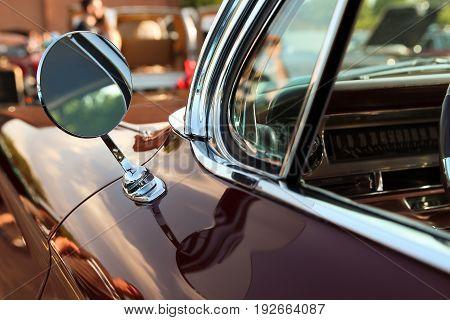 Classic retro vintage black car. Car mirror. The car is older than 1985.