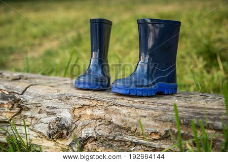 children's rubber boots stand on the beam ,the concept of camping and recreation