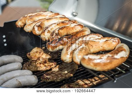 Barbecue grill bbq on propane gas grill. steaks bratwurst sausages meat meal