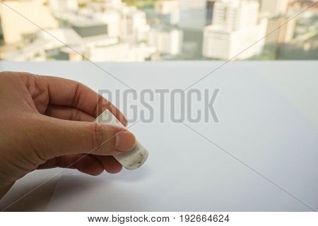 close up people hand use eraser on mock up paper sheet for mistake removal