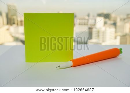 mock up postit on office desk with cute carrot pen for noting as reminder