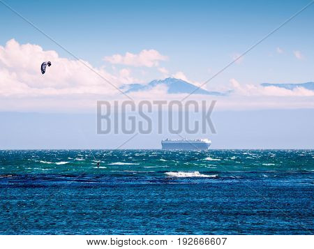 Large cargo ship in the Pacific Ocean against the mountain background kite surfer in the foreground