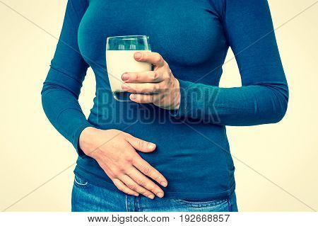 Woman with lactose problem is suffering from stomach pain isolated on white - dairy intolerance concept - retro style
