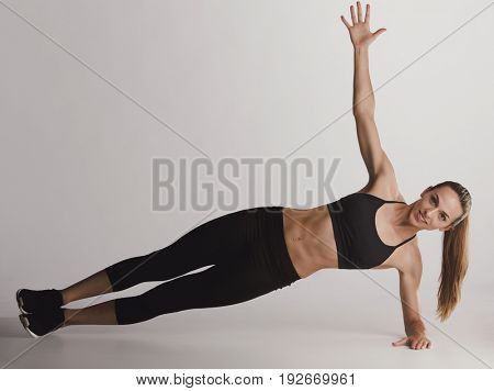 Shot of a young woman doing side plank exercises