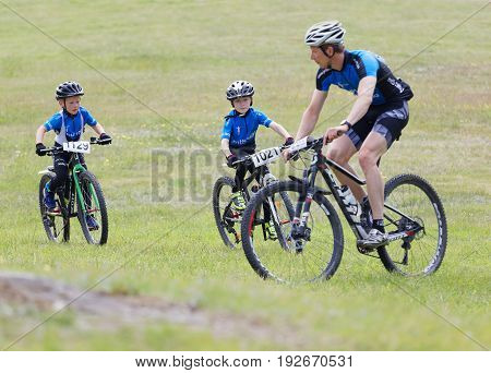 STOCKHOLM SWEDEN - JUNE 11 2017: Family with father and his two kids cycling on mountain bikes on the meadow at Lida Loop Mountain bike Race. June 11 2017 in Stockholm Sweden
