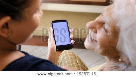 Girl Helping Old Woman Using Mobile Phone And Technology