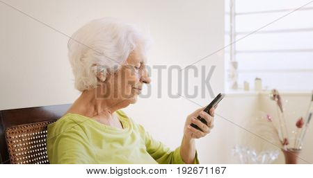 Happy old woman using smartphone touching the screen and playing the phone at home.