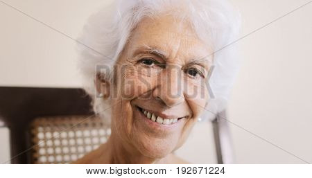 Portrait of old lady sitting on rocker at home. Happy senior woman relaxing on rocking chair and smiling at camera.