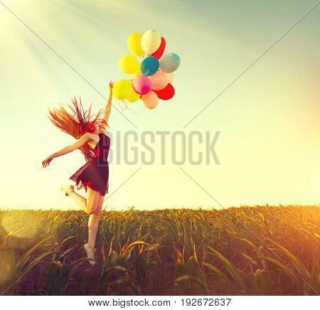 Beauty redhead girl running and jumping on summer field with colorful air balloons over Sunset clear sky. Happy young healthy woman enjoying nature outdoors. Running and Spinning female. Flying away
