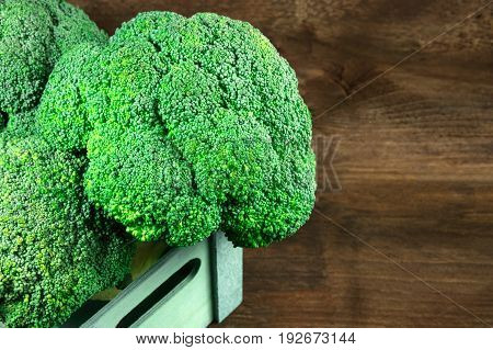 A photo of broccoli heads in a crate on a dark rustic texture with a place for text