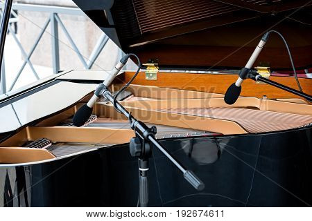 Piano With Open Lid. Two Microphones Above The Strings Of Black Grand Piano.