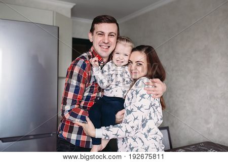 Happy young parents with their little daughter having fun at home