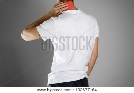 The Guy In White T-shirt Clings To The Back Of The Head. Pain In The Back Of His Neck