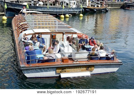 NYHAVN, COPENHAGEN - JULY 12, 2016: A guided tour on a small boat around Nyhavn waterway sites, Nyhavn, Copenhagen, Denmark