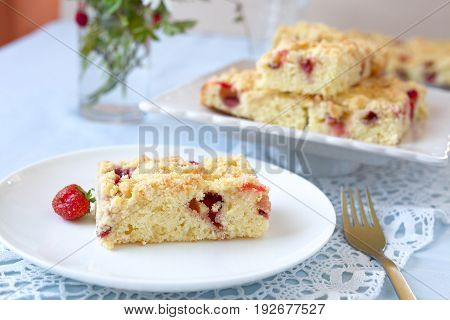 Slice of crumble strawberry cake on a white plate.