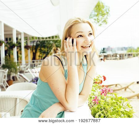 portrait of pretty modern girl friend in cafe open air interior drinking and talking on phone smiling, having chat and coctail, lifestyle friendship people concept close up